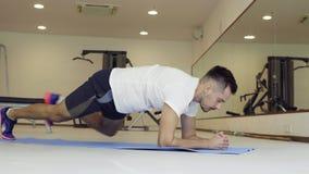 Человек делая динамическую планку в спортзале Расположите планку на пол с локтями и пальцами ноги сток-видео
