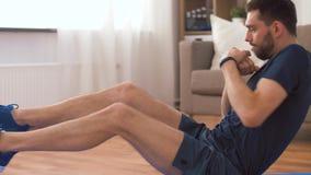 Человек делая подбрюшные тренировки дома сток-видео