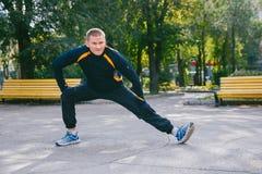 Человек делая подогрев в парке Здоровый уклад жизни Стоковое Фото