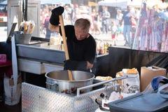Человек делая попкорн на ярмарке стоковое фото rf