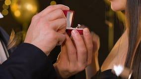 Человек делая предложение на партии xmas и давая драгоценное кольцо к удивленной даме видеоматериал