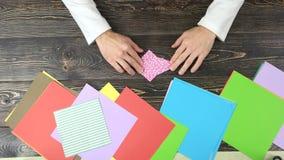 Человек делая розовый бумажный кран сток-видео