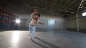 Человек делая элементы capoeira в комнате с конкретным полом, кирпичными стенами и ярким светом сток-видео