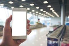 Человек держа белый мобильный телефон с пустым белым экраном пока стоящ и ждущ заявка багажа в авиапорте стоковое изображение rf