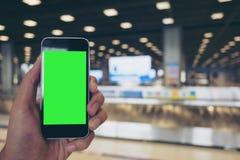 Человек держа белый мобильный телефон с пустым зеленым экраном пока стоящ и ждущ заявка багажа в авиапорте стоковое изображение