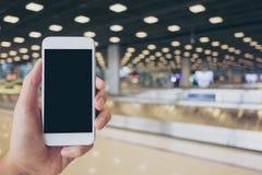 Человек держа белый мобильный телефон с пустым черным экраном пока стоящ и ждущ заявка багажа стоковая фотография