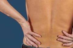 Человек держа его тягостную воспламененную поясницу на голубой предпосылке Здравоохранение и микстура Страдать от боли в спине стоковое фото rf