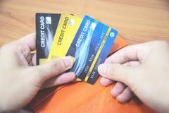 Человек держа кредитную карточку в руке - онлайн оплачивать от домашней или увеличенной концепции кредитной карточки задолженност стоковые фото
