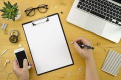 Человек держа мобильный телефон и место для работы стола домашнего офиса ручки с руками ` s человека, серебряной тетрадью и офисо Стоковая Фотография