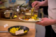 Человек держа плиту еды vegan и лить еду Стоковое Фото
