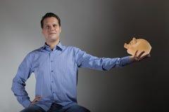 Человек держа предпосылку темноты piggy банка Стоковое фото RF