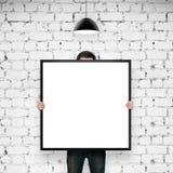 Человек держа рамку в комнате кирпича Стоковое Изображение