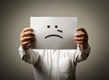 Человек держит белую бумагу с улыбкой Плача концепция Стоковое Изображение