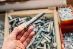 Человек держит болт здания Много различных инструментов крепления используемых в конструкции и ремонте Стоковое Фото