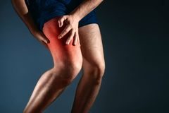 Человек держит дальше к колену, боли в колене Стоковые Изображения