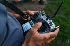 Человек держит дистанционное управление во время управления полетом трутни спорт Стоковое Изображение RF