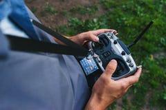 Человек держит дистанционное управление во время управления полетом трутни спорт Стоковые Изображения RF