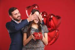 Человек держит его глаза подруги покрытый пока она давая подарок, романтичный сюрприз на день валентинок Стоковые Фото