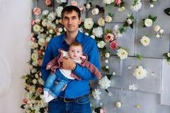 Человек держит его маленькую дочь Будьте отцом с младенцем в его оружиях против стены с цветками стоковые фото