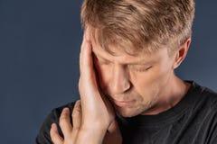 Человек держит его руки на его голове на голубой предпосылке Головная боль или мигрень стоковые фотографии rf