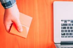 Человек держит жесткий диск external портативной машинки стоковое изображение rf