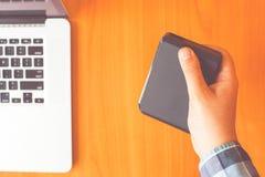 Человек держит жесткий диск external портативной машинки стоковое изображение