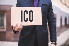"""Человек держит знак внутри его рука с монеткой Offerering надписи """"ICO """"начальной Запас Ind рынка цифров электронный торговый стоковая фотография rf"""