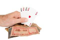 Человек держит игральные карты над кучей наличных денег стоковые фото