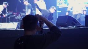 Человек держит камеру и принимает видео танцуя группы в составе молодые активные люди на этапе акции видеоматериалы