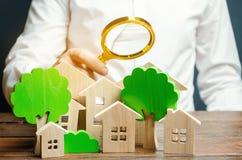 Человек держит лупу над деревянными домами и деревьями Валюация недвижимости и выбор места для конструкции стоковые фото