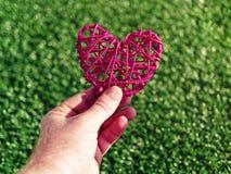 Человек держит плетеное сердце в руке против предпосылки зеленой травы Стоковая Фотография