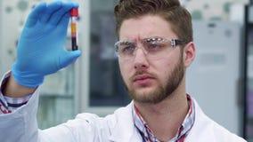 Человек держит пробирку в его руке на лаборатории стоковая фотография