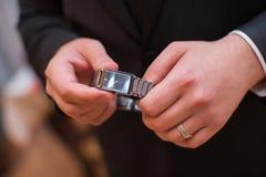 Человек держит руки часами и имеет кольцо в его руке Стоковое Изображение RF