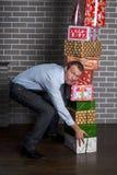 Человек держит стог подарочных коробок в его руках Стоковые Фото