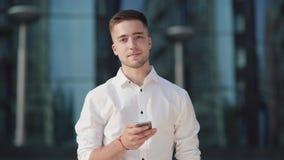 Человек держит телефон в правой руке, печатает SMS или серфинг интернета сток-видео
