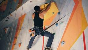 Человек держит утесы на взбираясь стене, clsoe вверх акции видеоматериалы