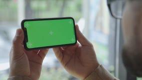 Человек держит smartphone с обеими руками Горизонтальная ориентация сток-видео