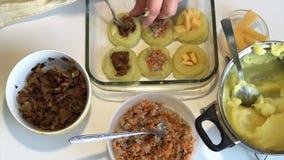 Человек добавляет грибы к croquettes картошки как завалка Рядом контейнеры с заполнять грибы, семенить мясо и chees сток-видео