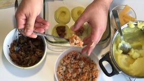 Человек добавляет заполнять к croquettes картошки как завалка Рядом контейнеры с заполнять грибы, семенить мясо и сыр видеоматериал