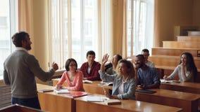 Человек добросердечного жизнерадостного учителя бородатый спрашивает вопросы проверяя знание пока студенты поднимают руки и отвеч сток-видео