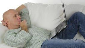 Человек дома сидя и отдыхая на софе делая дело используя ноутбук стоковая фотография