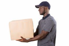 Человек доставки молодой в красной форме изолированной на белой предпосылке стоковое изображение rf