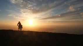 Человек едет велосипед высокий в горах над океаном против красивой драматической предпосылки захода солнца на острове Лансароте видеоматериал