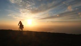 Человек едет велосипед высокий в горах около края скалы над океаном пр сток-видео