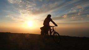 Человек едет велосипед высокий в горах около края скалы над океаном против красивой драматической предпосылки захода солнца акции видеоматериалы
