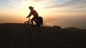 Человек едет велосипед высокий в горах около края скалы над океаном против красивой драматической предпосылки захода солнца видеоматериал