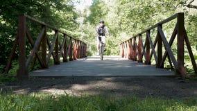Человек едет велосипед в парке В временени акции видеоматериалы