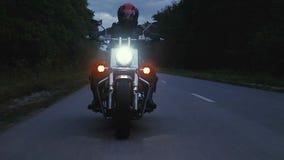 Человек едет мотоцикл вниз с дороги в лесе Стоковые Фотографии RF