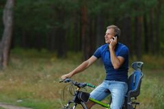 Человек едет на велосипеде в лесе и говорит телефоном Стоковые Фото