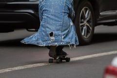 Человек едет скейтборд сидя на разделяя прокладке на улице города стоковое изображение
